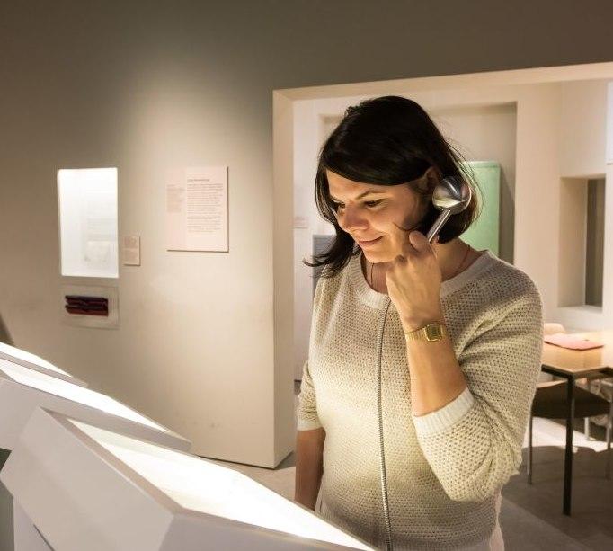 Eine Besucherin mit einem Hörlöffel in der Dauerausstellung