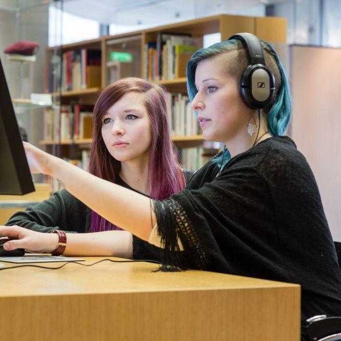 Besucherinnen im Informationszentrum bei der Recherche am Computer.