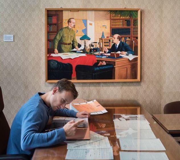 Ein Besucher sitzt an einem Schreibtisch in der Dauerausstellung