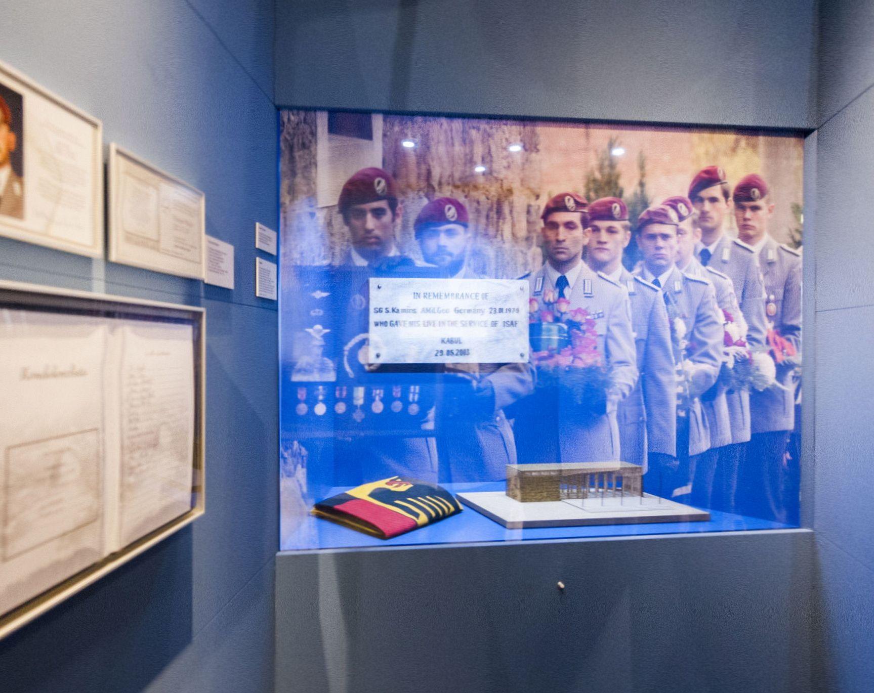 Blick in eine Ausstellungseinheit mit einem großformatigen Foto von Soldaten in einem Trauerzug, einem Architekturmodell, einer zusammengefalteten Deutschlandflagge, einer Traueranzeige und weiteren Dokumenten