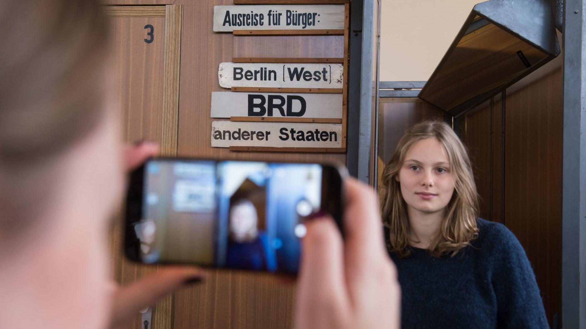 Im Hintergrund eines junges Mädchen das in einem Türrahmen posiert für eine Kameraaufnahme mit dem Smartphone, das man im Vordergrund des Bildes sieht