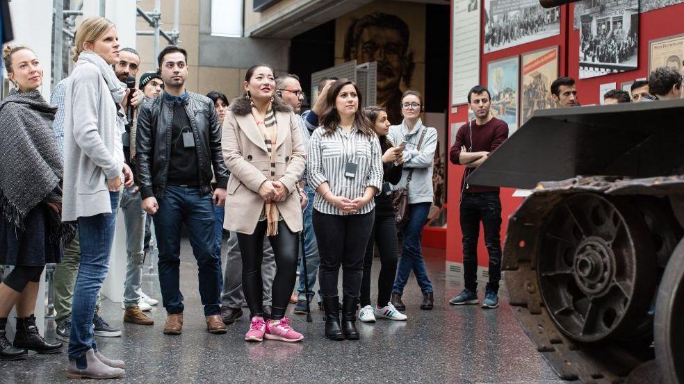 Eine Gruppe junger Erwachsener steht in der Ausstellung dem Betrachter zugewandt, recht im Bild der vordere Teil eines Panzers