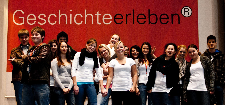Gruppenbild der TeenGroup 2010/2011 vor dem Plakat 'Geschichte erleben'