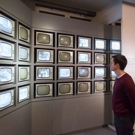 Ein Besucher betrachtet eine Wand mit Fernsehern in der Dauerausstellung in Leipzig