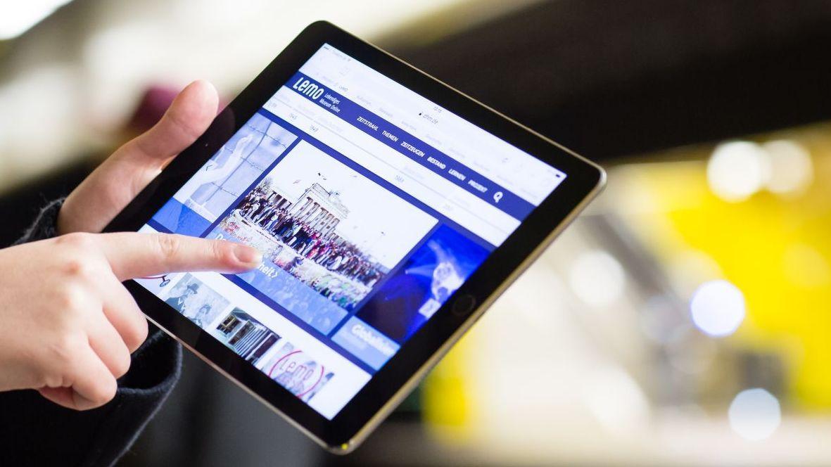 Im Zentrum des Bildes ein Tablet mit der Startseite des Internetportals LeMO, das eine junge Frau hält, im Hintergrund eine U-Bahn-Station