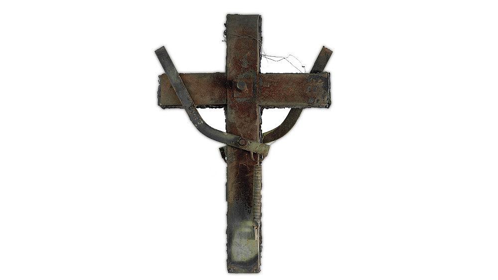Stahlkreuz, das aus Teilen von typischen DDR-Müllcontainern geschweißt wurde. Vorder- und Rückseite sind gleich gestaltet. Auf das Kreuz ist zusätzlich eine Metallfeder mit einem Bügel montiert.