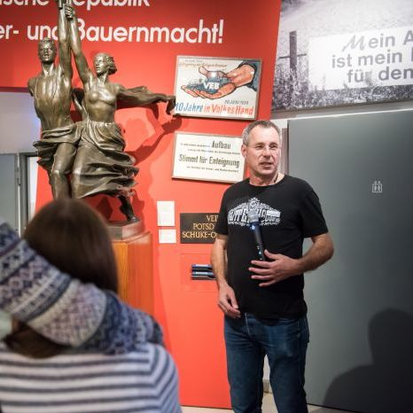 Ein Gruppenbegleiter spricht zu Besuchern in der Dauerausstellung