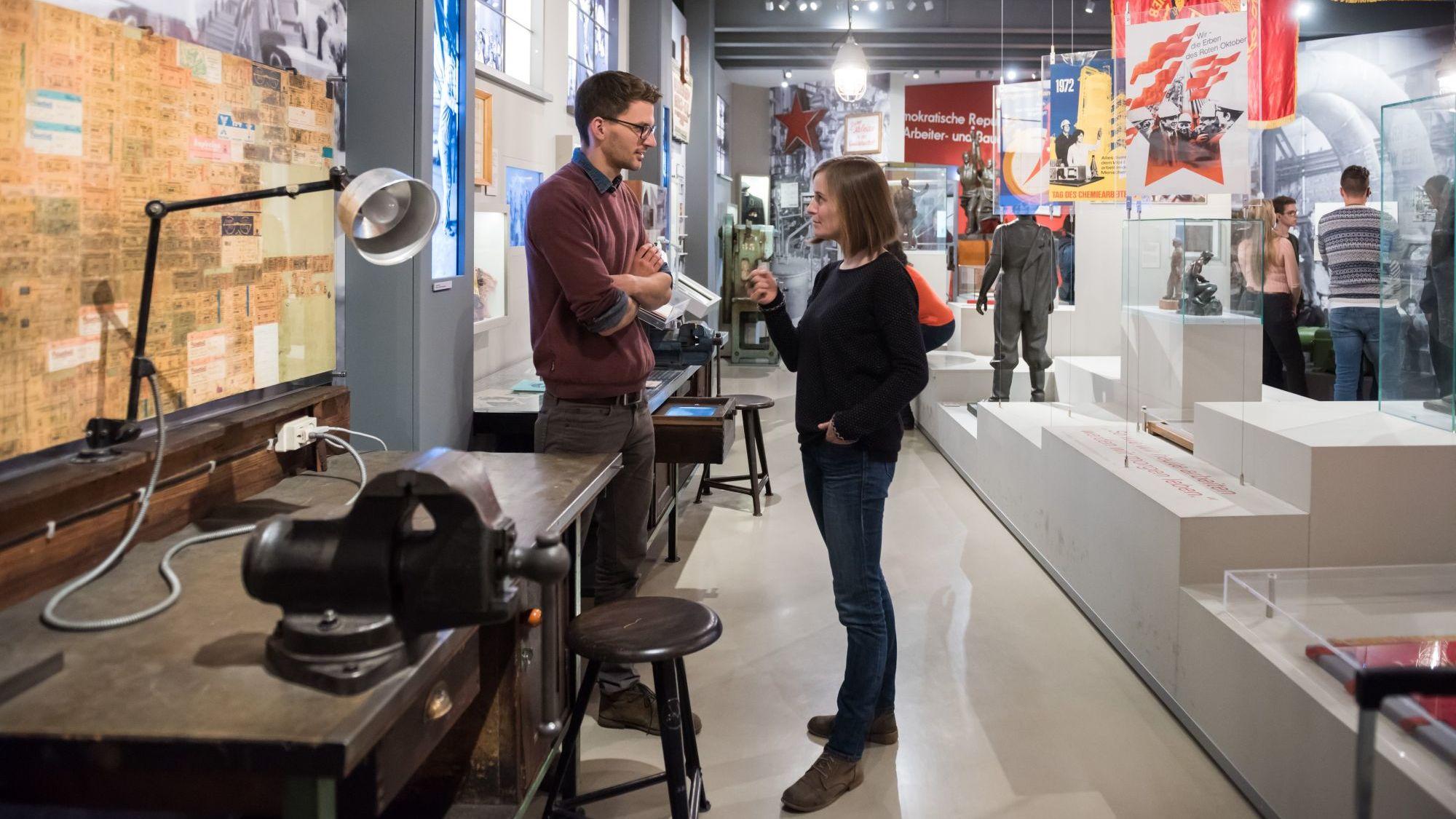 Eine junge Frau und ein junger Mann stehen in einem großen Raum, links vorne ein Werkbank, im Hintergrund unter anderem Fahnen und andere Besucher