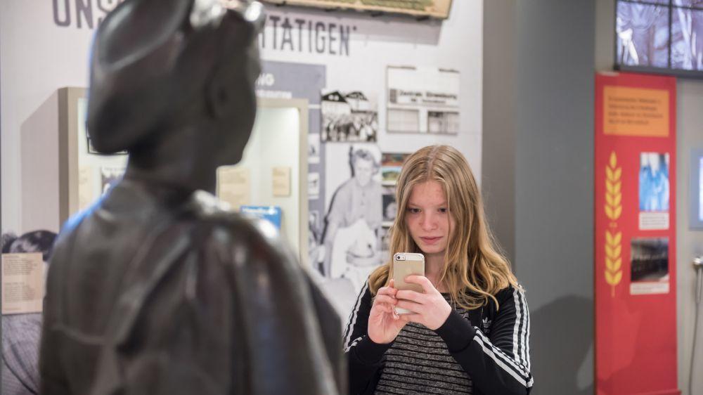 Ein Mädchen fotografiert in der Dauerausstellung eine Skulptur