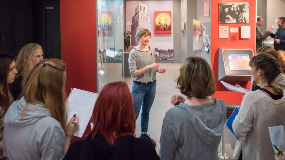 Eine Begleiterin im Museum zeigt eine Medienstation