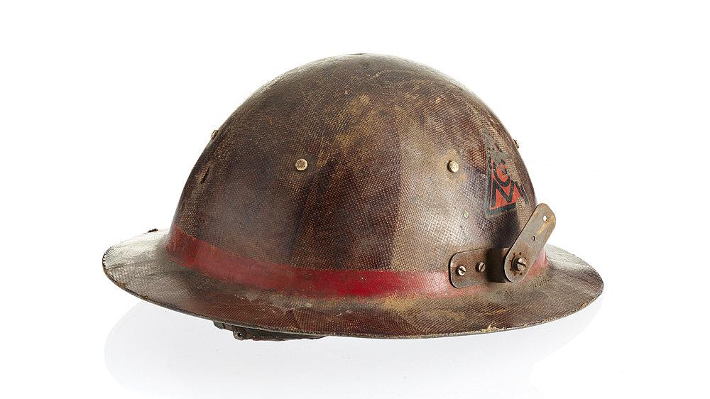 Braun-roter Helm mit flacher, schmaler Hutkrempe. Außen am Übergang von Krempe zu Helmaufsatz roter Streifen. An beiden Seiten angeschraubte Metallverstrebungen, vermutlich zur Befestigung weiterer Schutzvorrichtungen.