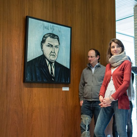 Besucherin und Besucher vor einem Porträt Ludwig Erhards