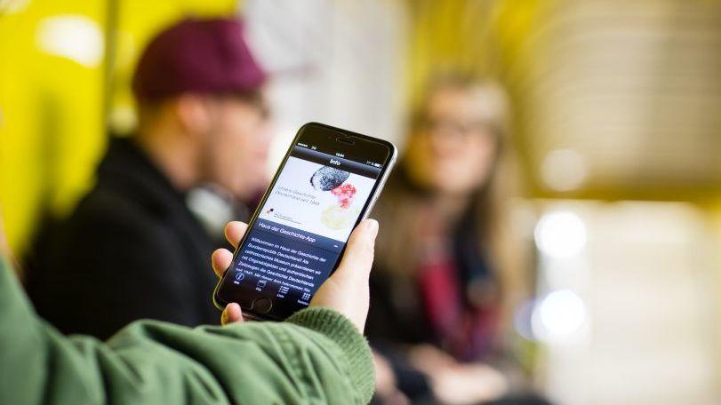 Eine Hand hält ein Smartphone mit dem Audioguide in der U-Bahn