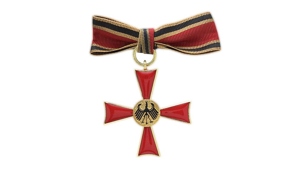 Goldfarben eingefaßtes, rot emailliertes Kreuz mit goldfarbenem Medaillon. Darauf schwarzer erhabener Bundesadler. Auf dem oberen Kreuzarm Öse mit Bandring. Rote Damenschleife mit gold-schwarz-goldfarbenen Seitenstreifen.