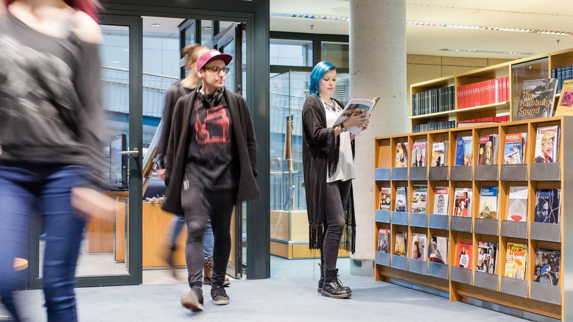 Besucher im Informationszentrum vor dem Zeitschriftenregal.