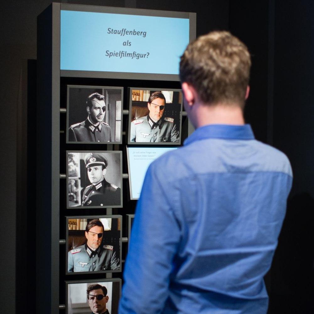 Ein junger Mann steht mit dem Rücken zum Betrachter vor einer Wand, die verschiedene Schauspieler in der Rolle des Claus Schenk Graf von Stauffenberg zeigt