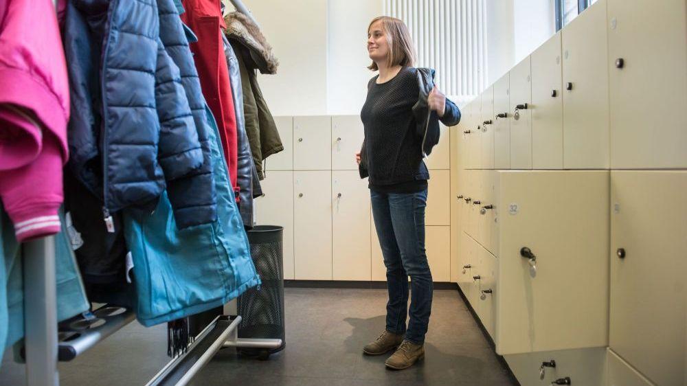 Eine Frau zieht eine Jacke in der Garderobe an