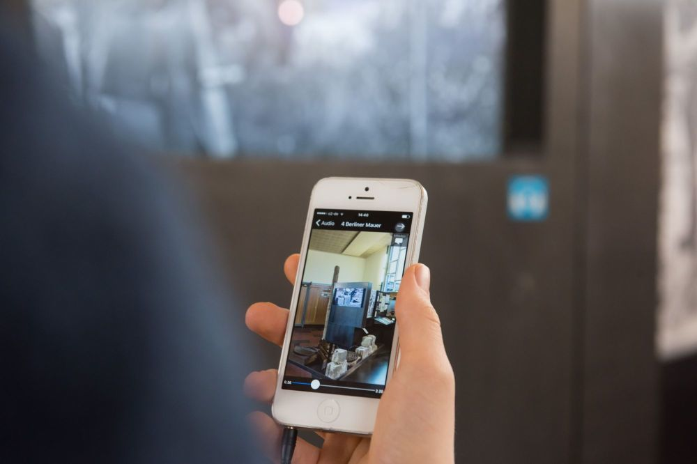 Eine Hand mit einem Smartphone, auf dem Screen ein Foto aus der Ausstellung im Tränenpalast
