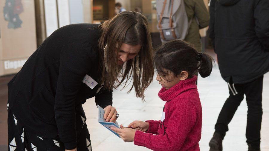 Eine Frau beugt sich im Tränenpalast zu einem kleinen Mädchen hinunter und schaut mit ihm in ein kleines Heft