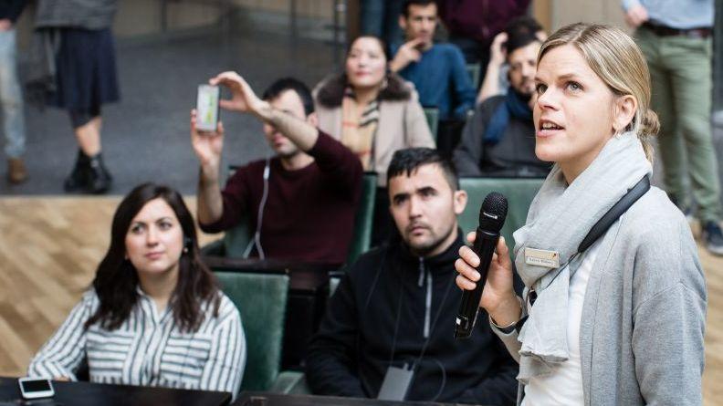 Im Vordergrund eine junge Frau mit Mikrofon, dahinter sitzen junge Erwachsene in der Ausstellung, hören zu und machen Fotos