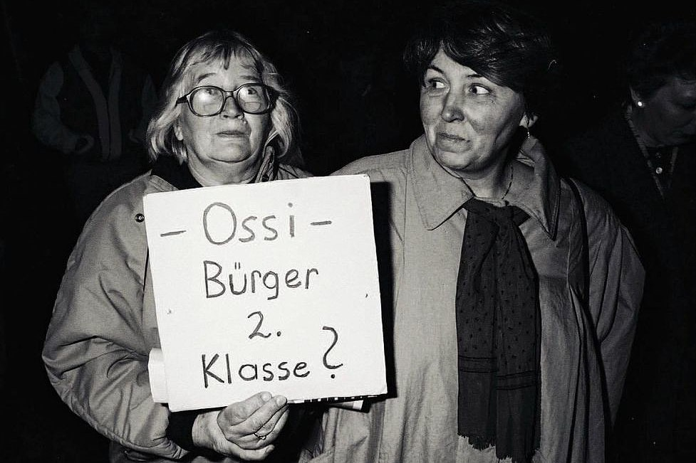 Zwei Frauen, eine davon trägt ein Plakat mit der Aufschrift - Ossi - Bürger 2. Klasse?