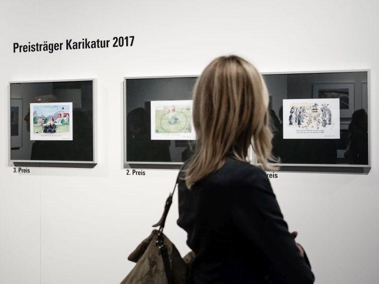 """Besucherin betrachtet die """"Preisträger Karikatur 2017"""""""
