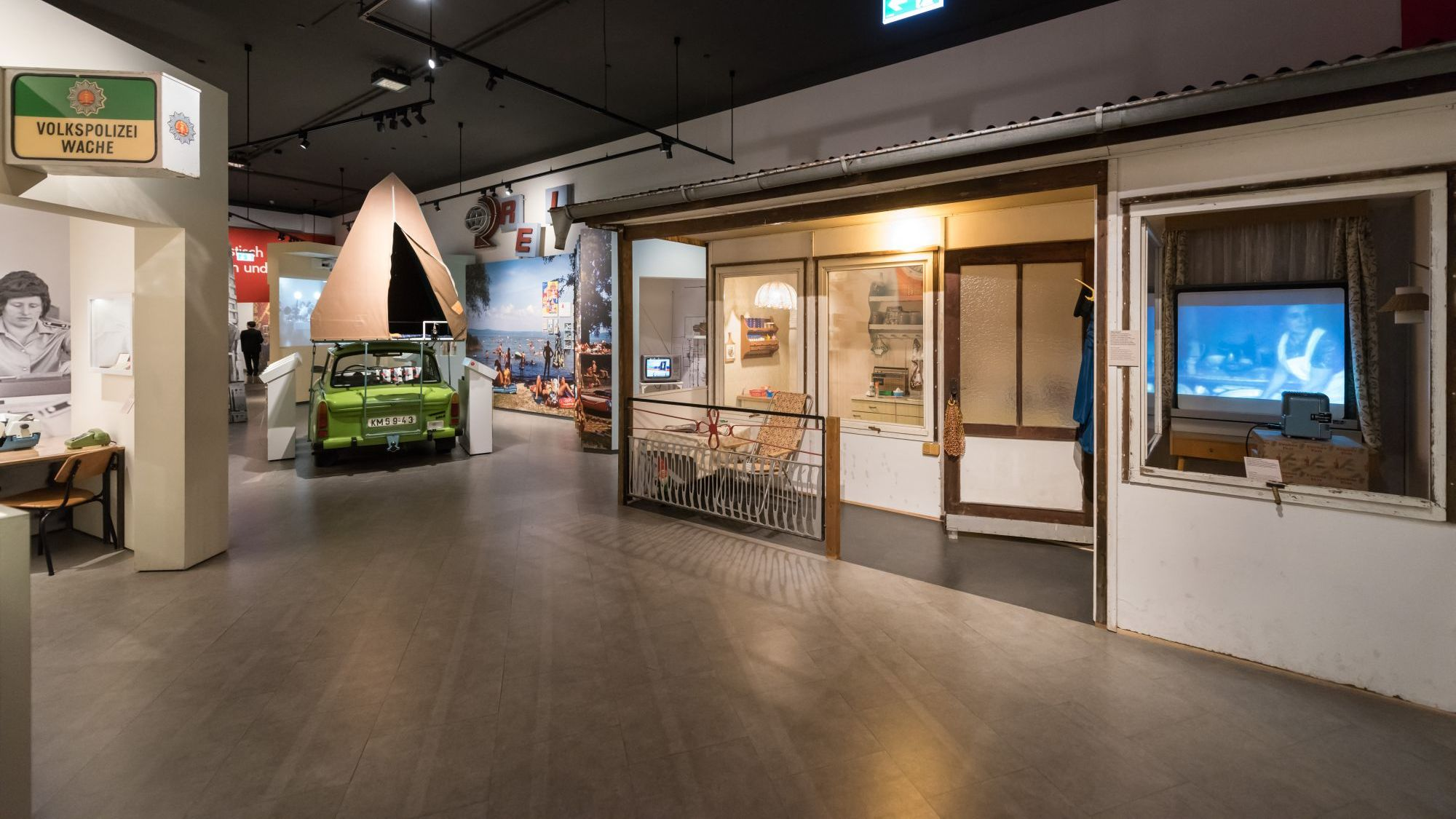 View into an exhibition room with a summer house and a Camping-Trabi