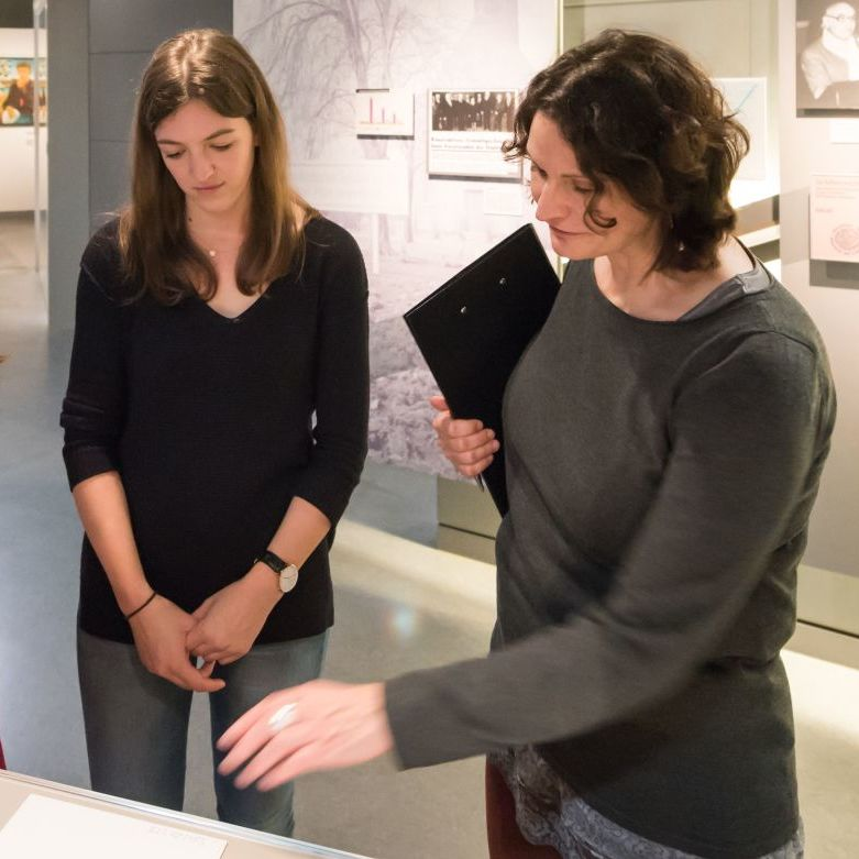 Besucherinnen lesen Materialien in der Ausstellung