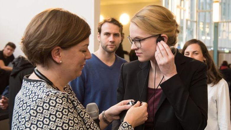 Eine junge Frau befestigt den Ohrstecker den Audio-Gruppenführungssystems, eine andere Frau hilft ihr dabei
