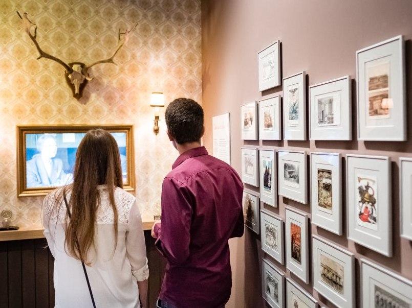 Eine Besucherin und ein Besucher neben einer Wand mit Bildern