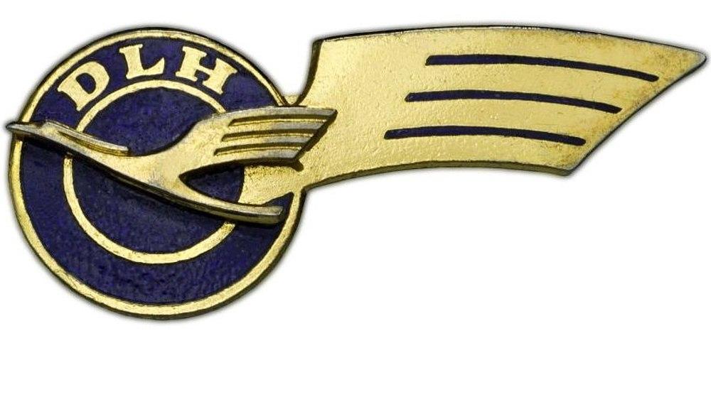 Rundes, blaues Abzeichen mit goldfarbenem Kranich und Buchstaben 'DLH', rechts ragt eine goldfarbene Schwinge heraus.