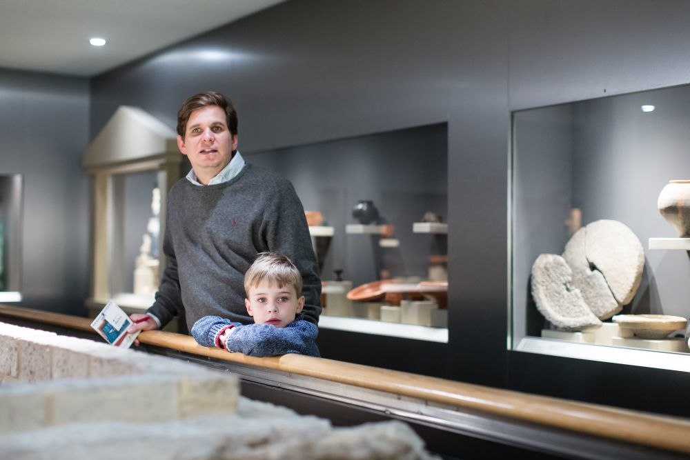 Ein kleiner junge und ein Mann stehen an einem Geländer. Hinter ihnen sind große Schaukästen in einer Wand zu sehen mit Vasen und einem zerbrochenen Mühlstein