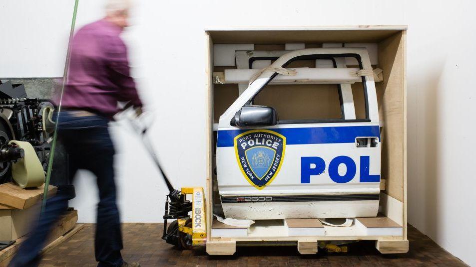 Ein Mitarbeiter räumt eine Polizeiautotür um