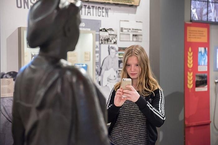 Eine Besucherin fotografiert eine Skulptur in der Dauerausstellung