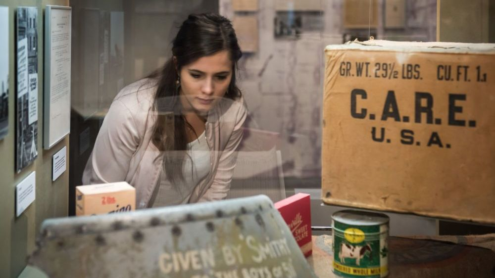 A girl is looking at a CARE package in the exhibition