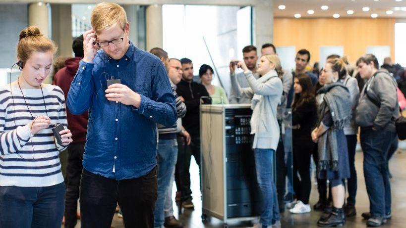 Im Vordergrund eine junge Frau und ein junger Mann, die ihre Geräte und die Ohrhörer für die Begleitung anbringen, im Hintergrund weitere Personen bei der Ausgabe der Geräte
