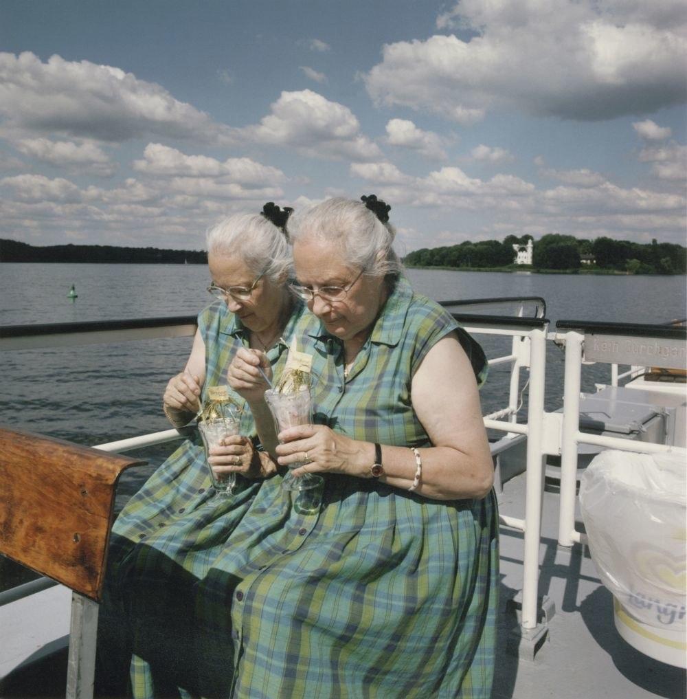 Zwei alte Zwillingsschwestern sitzen mit gleichen Kleidern und Frisuren auf einem Bootsdeck und trinken aus geschmückten identischen Gläsern, hinter ihnen Wasser und Himmel