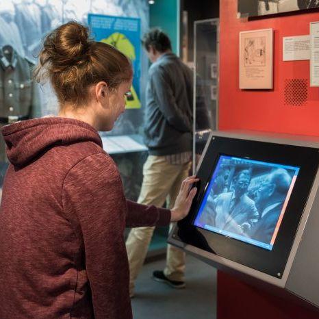 Eine Besucherin sieht einen Film in einem Monitor in der Dauerausstellung