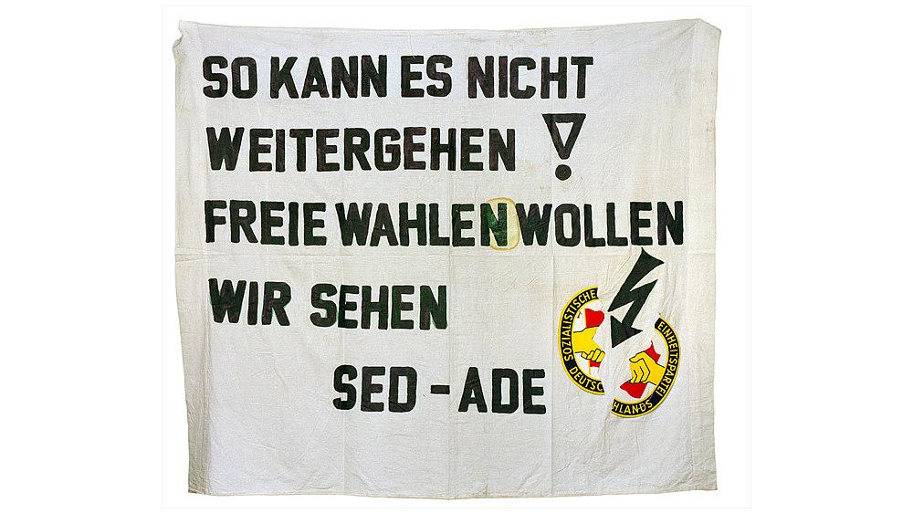 Auf einem weißen Bettlaken steht geschrieben So kann es nicht weitergehen! Freie Wahlen wollen wir sehen SED Ade