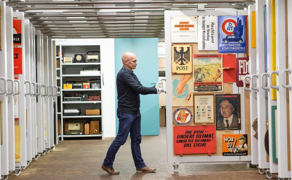 Ein Mann zieht in einem großen Raum eine rollbare Zwischenwand heraus, an der Schilder mit unterschiedlichen Motiven und Aufschriften hängen.