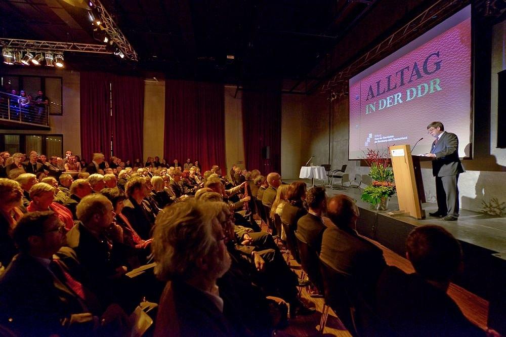 Stiftungspräsident Hütter auf einer Bühne, hinter ihm das Plakat der Ausstellung Alltag in der DDR, vor der Bühne sind Stuhlreihen mit Menschen