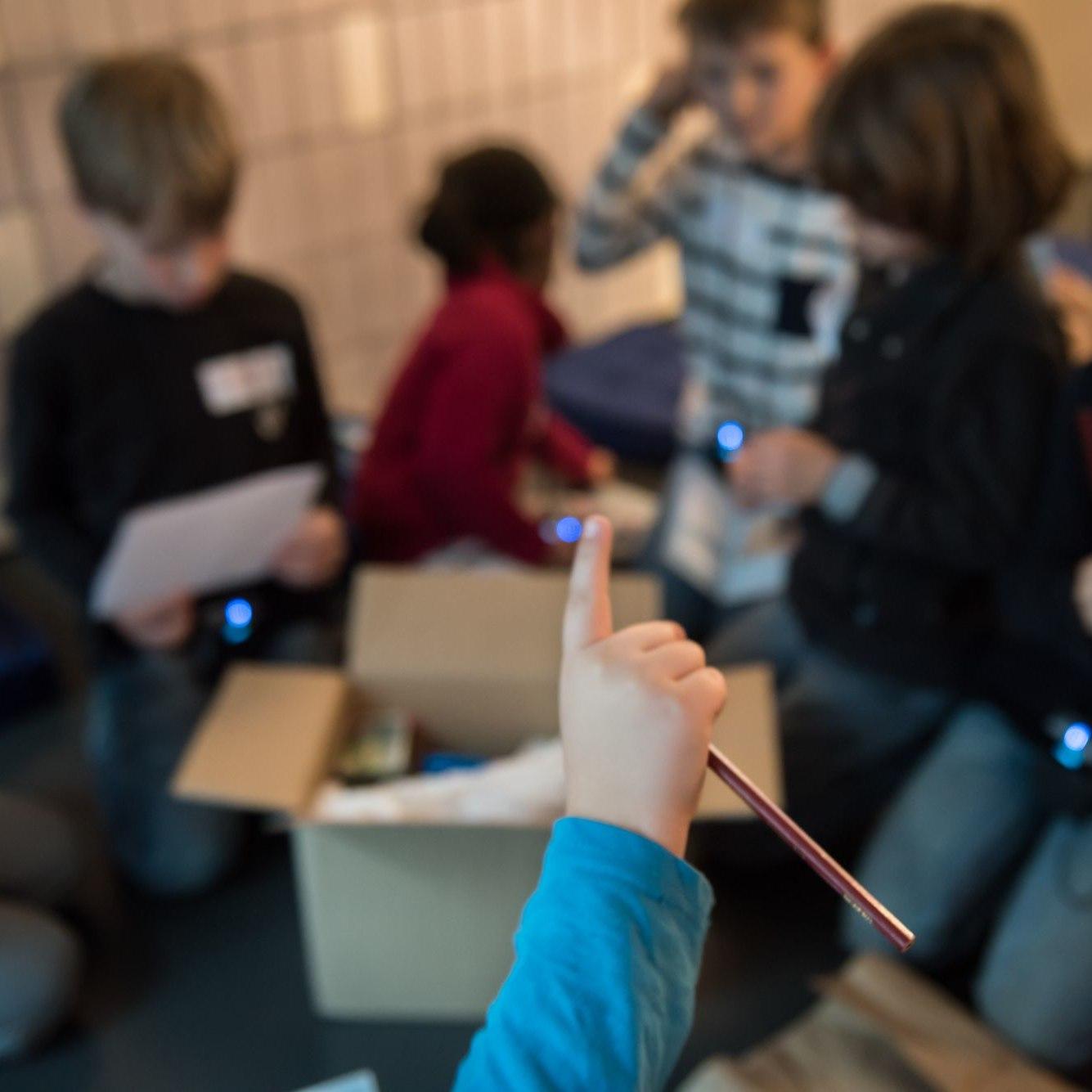 Im Hintergrund knieen Kinder vor einem geöffneten Paket, im Vordergrund eine Hand mit Stift und ausgestrecktem Zeigefinger