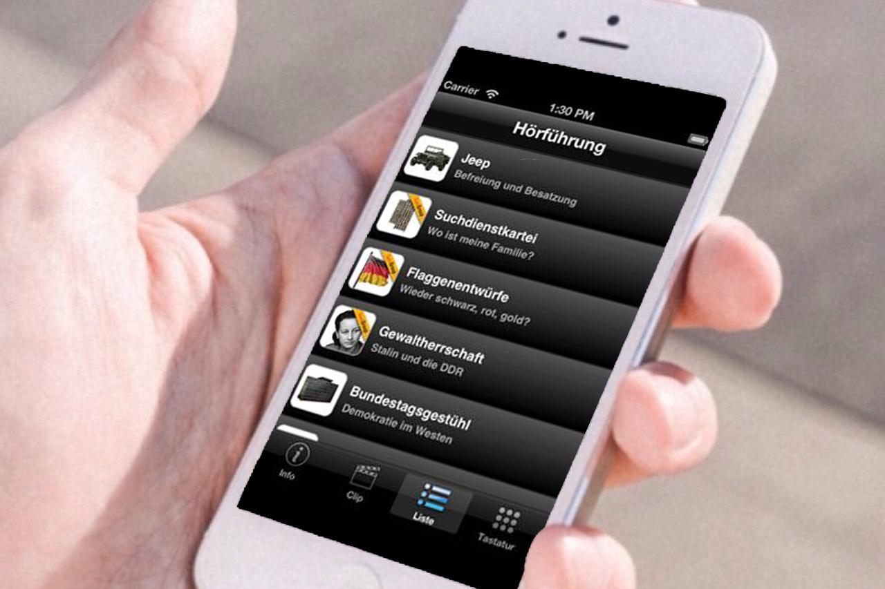 Hand mit Smartphone, auf dem die App zu Dauerausstellung im Haus der Geschichte in Bonn zu sehen ist