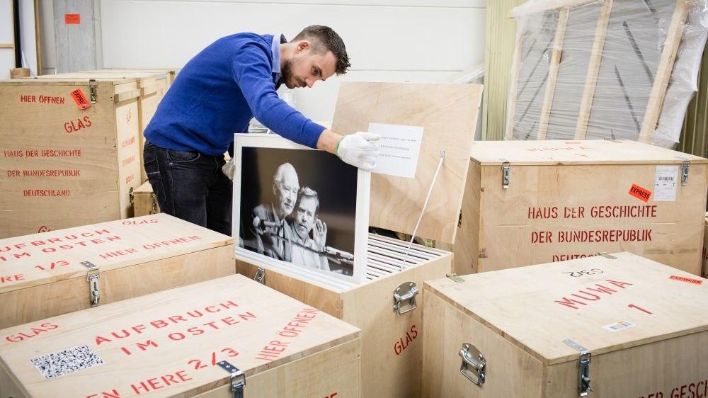 Ein junger Mann verstaut ein großeformatiges, gerahmtes Foto in einer offenen Holzkiste. Um ihn herum stehen weitere geschlossene Holzkisten