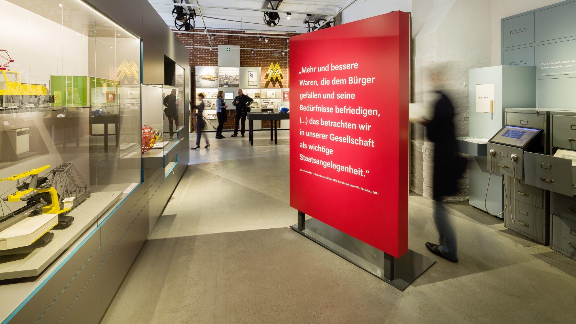 Blick in einen großen Ausstellungsraum, in der Mitte ein großer roter Raumtrenner mit einem Zitat von Erich Honecker, links Modelle von Nutzfahrzeugen in einer Vitrine