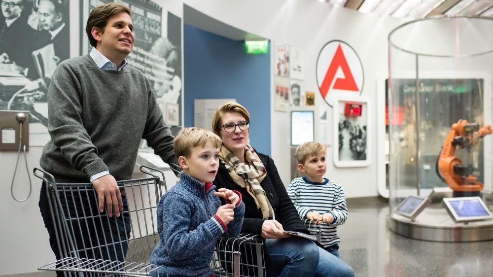 Eine Junge und seine Mutter sitzen in einem Ausstellungsraum auf Stühlen in Form von Einkaufswagen, der Vater steht dahinter, ein anderer kleiner Junge daneben