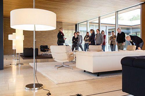 Eine Besuchergruppe steht vor einer Sitzgruppe im Empfangsbereich des Kanzlerbungalows in Bonn