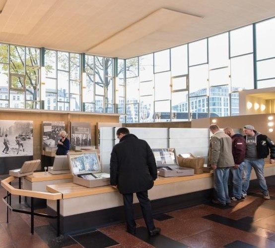 Besucher betrachten Medienstationen und Objekte in der Dauerausstellung des Tränenpalasts