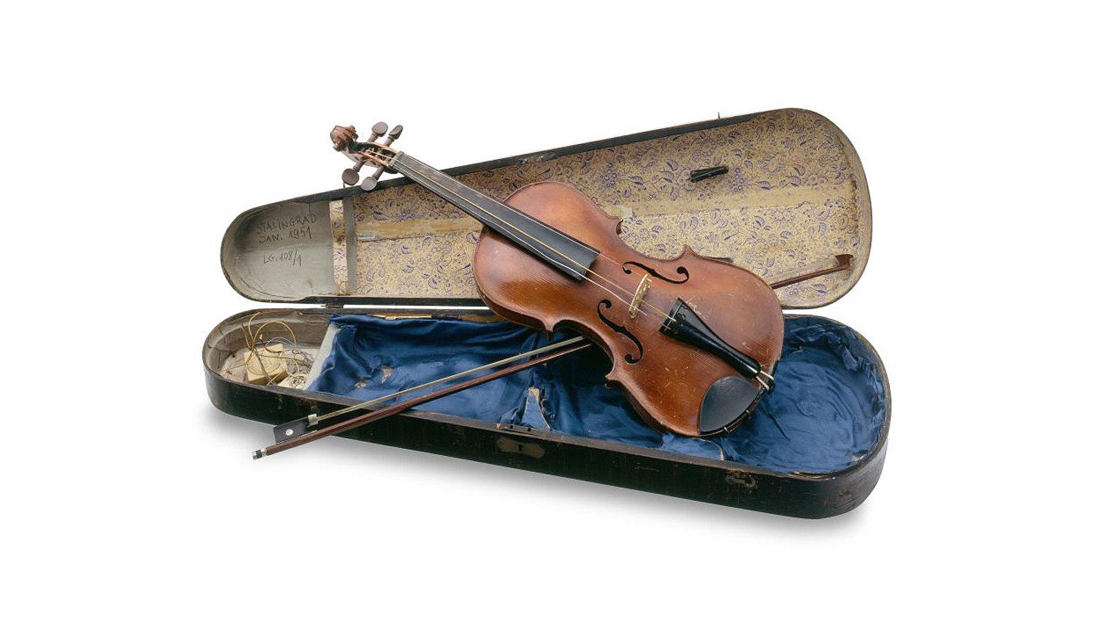 Geige mit Geigenkasten, die stark beschädigt die Schlacht von Stalingrad überstand