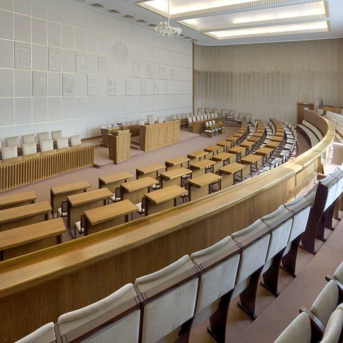 Blick in einen großen länglichen Raum, Sitzreihen laufen auf den Betrachter zu und sind einem Rednerpult und zwei weiteren Sitzreihen zugewandt